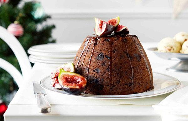 A boiled Christmas pudding, studded with dried fruit, topped with sliced figs and drizzled with a dark-brown port syrup, on a white plate, on a white table.