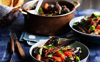 In the foreground, a grey dish holding a pile of steamed mussels with chopped tomatoes and basil, on a dark blue tablecloth. In the background, a copper pot holding more of said mussels.