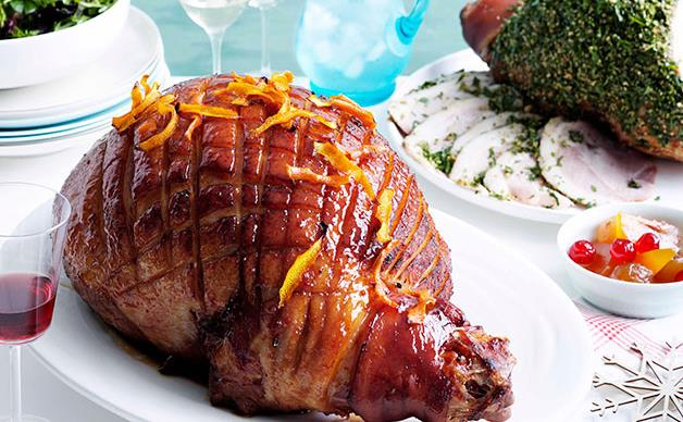 A leg of ham, scored, brushed with a sticky glaze, and sprinkled with orange rind.