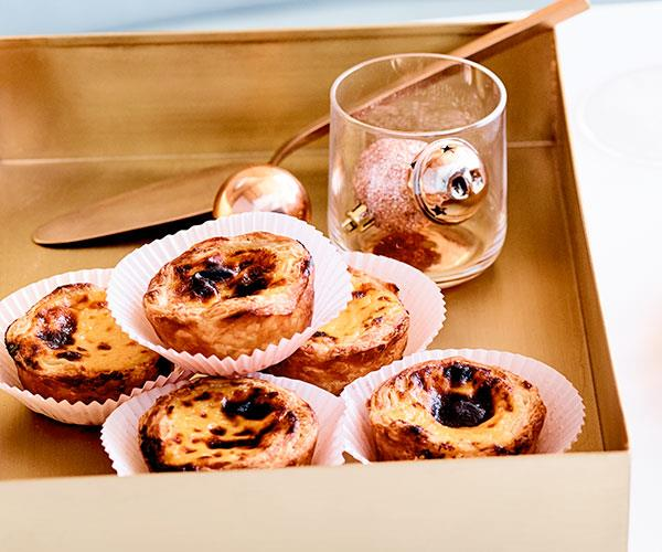 Golden square tin holding hand-sized custard tarts with burnished tops, each in their own white paper casing. There's also a glass holding a rose-pink speckled bauble, which is kind of weird, but we'll take it.