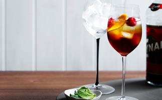Tall, stemmed wine glass of Cynar Spritz, a red-brown coloured libation with ice cubes, orange peel and a cherry.