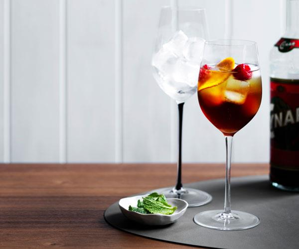 Tall wine glass filled with a brown-coloured spirit, ice, orange slices and red berries. Small plate of mint leaves is placed to the side.