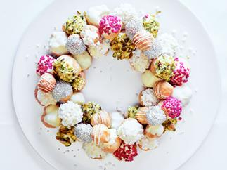 An over-the-top image of a wreath fashioned from an assortment of profiteroles, decorated in crystallised rose petals, silver cachous and pearl sugar, set on a snow-white plate.