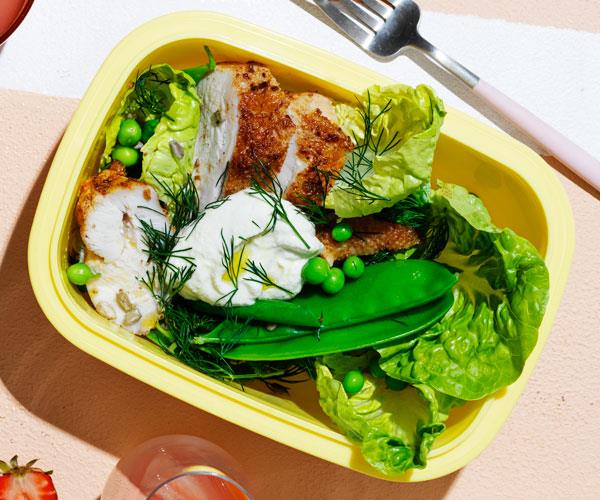 Roast chicken salad with peas and almond-lemon dressing in a yellow lunchbox