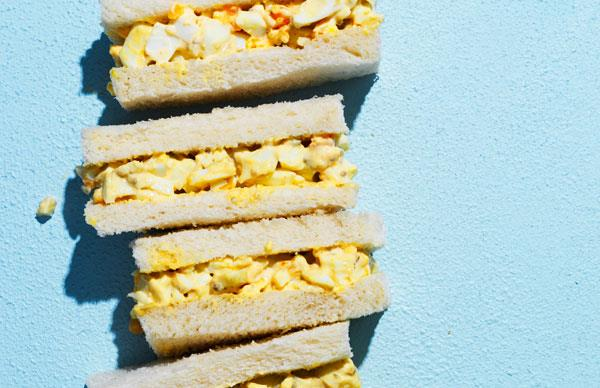 A stack of Japanese egg sandwiches on a blue background.