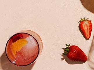 Glass of Rosé Spritz with strawberries on the side.
