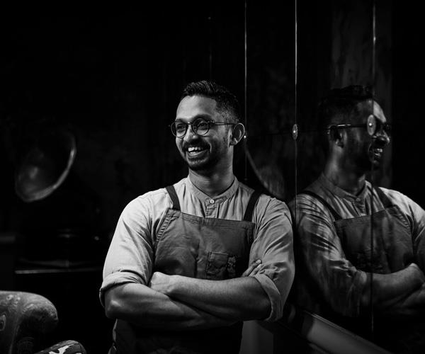 Black and white portrait of chef Rishi Naleendra leaning against a reflective wall.