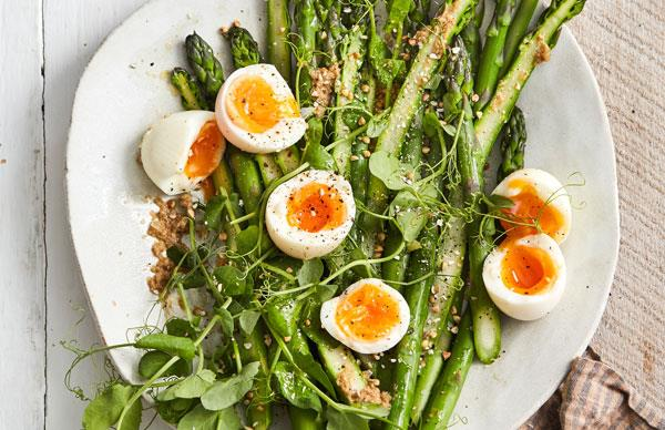 White plates with asparagus spears, halved soft-boiled eggs, and pea shoots, scattered with buckwheat.