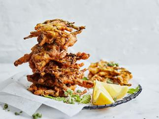 Fried zucchini fritters with wedges of lemon, stacked on a plate lined with white baking paper, on a white background.
