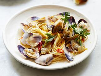 A white plate holding spaghetti, clams, chilli and flat-leaf parsley.