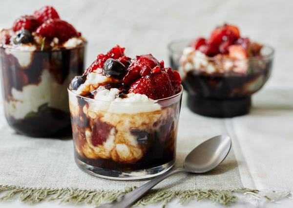 Three glasses, one in the foreground, two in the back, holding a tumble of mixed berries, goat's curd and balsamic vinegar. A spoon lies in the foreground.