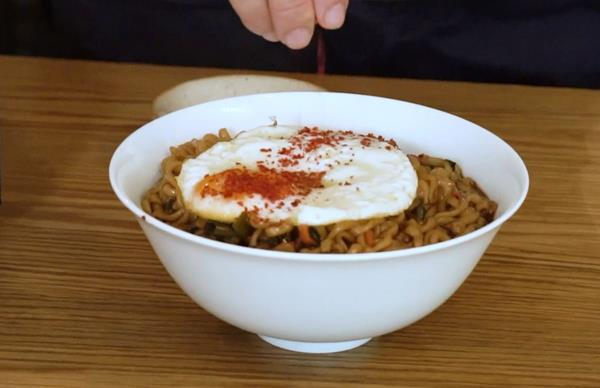 A white bowl holding jjapaguri noodles and a fried egg, with a hand sprinkling gochugaru Korean chilli flakes on top.