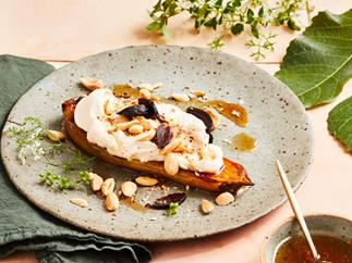 A thick slice of charred eggplant, topped with a thick white sauce and almonds, on a marbled grey plate, surrounded by a green linen napkin and green foliage.