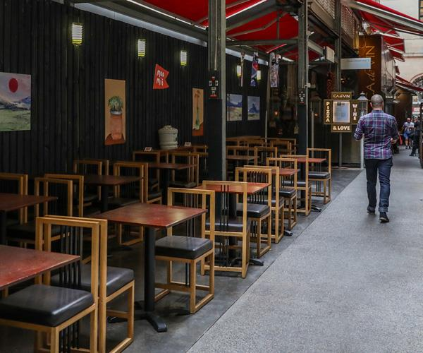 Unoccupied dining tables and chairs at a restaurant in the Melbourne CBD.