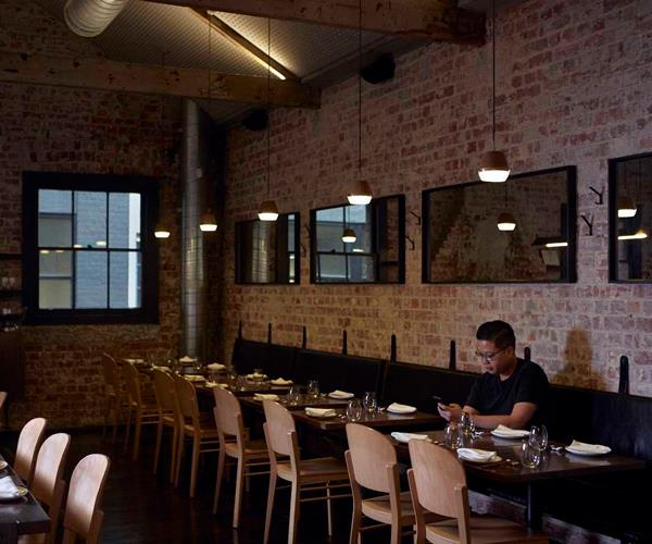 Chef Victor Liong sitting alone in an empty dining room.