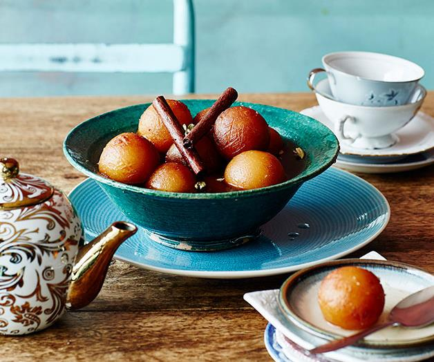 A aqua-blue bowl holding spheres of gulab jamun in syrup, garnished with two cinnamon sticks