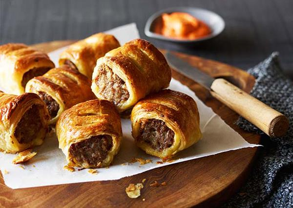 Mini sausage rolls on a square of white paper on a round wooden cutting board.