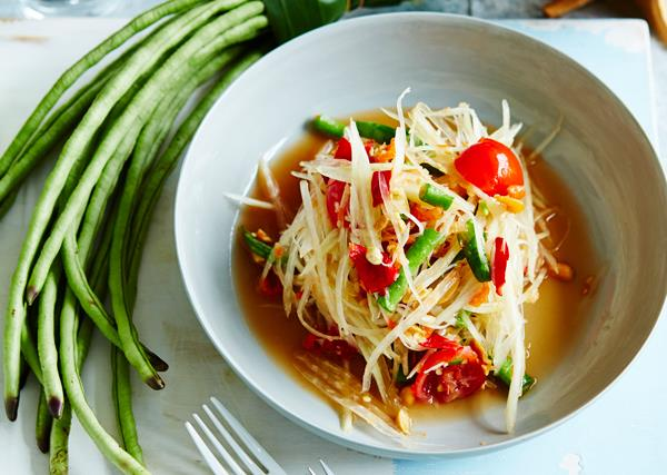 White bowl holding a salad of shredded green papaya, chopped green beans and halved cherry tomatoes. A bunch of snake beans is placed to the side.