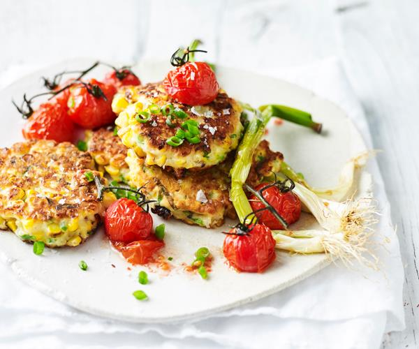 A white plate with fried corn fritters and roasted cherry tomatoes, garnished with chopped and whole shallots.
