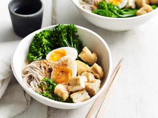 A white bowl with soba noodles, egg, tofy and broccolini, with a pair of wooden chopsticks on the side