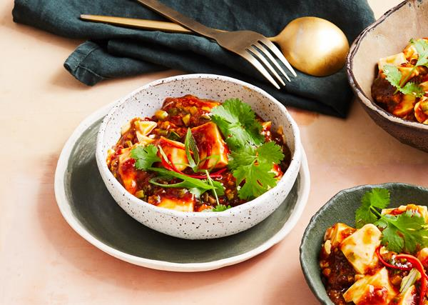 Ma po tofu in a white bowl with a green napkin and brass cutlery in the background