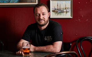 Chef Nik Hill sitting at a round table, with a beer in hand, with a red wall in the background.