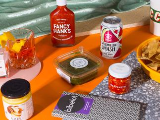 An assortment of grocery items – a bottle of chilli sauce, ghee, chocolate, dip – on an orange table