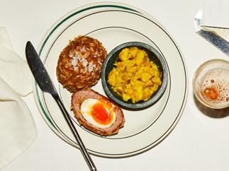 A halved Scotch egg, with a runny yolk centre, with a bowl of yellow-coloured cauliflower pickle, on a white round plate with a thin green border, on a white table. A stainless steel butter knife lies to the left, a glass of beer on the right.
