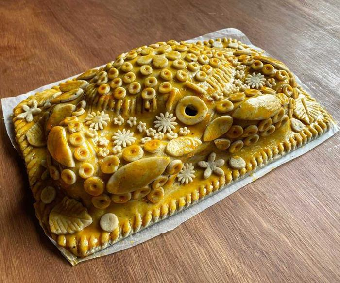 A whole mud crab, draped in baked pastry, and decorated with pastry flowers, circles and patterns. It sits on a brown wooden table.