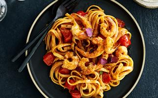 A black plate holding fettuccine, prawns and chunks of tomato, with a black fork and spoon to the side.