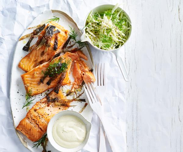 Three portions of ocean trout topped with strips of crisp fish and dill, with a bowl of yoghurt, on a white oval platter. A bowl of shredded kohlrabi is position at the top-right.