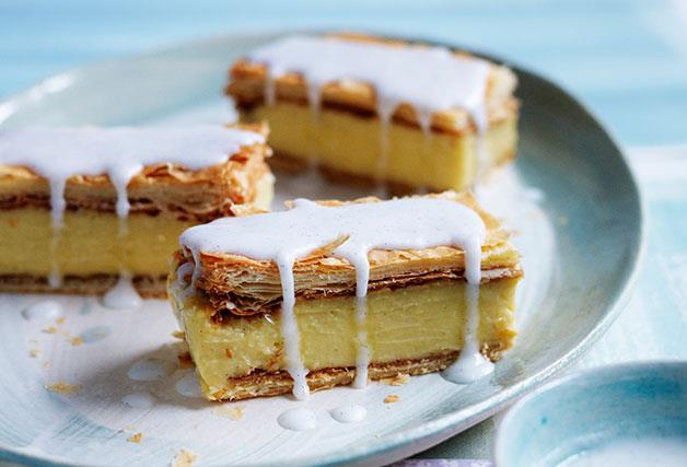 Three pieces of vanilla slice (custard sandwiched in pastry), drizzled with icing, on a blue and white plate.