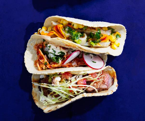Bird's eye shot of three tacos, filled with calamari and corn, spiced chicken and radish, and beef, on a dark blue background.