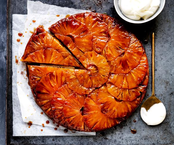Upside-down tart with caramelised pineapple slices layered on top, with a triangular slice detached from the tart.