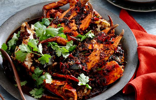 A grey plate holding cooked crab pieces covered in a black pepper sauce and garnished with coriander. A red napkin is arranged on the side.