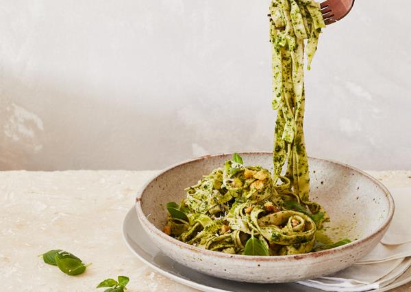 A raised fork dangling strands of long pasta coated in a green herb sauce, from a brown-white bowl.