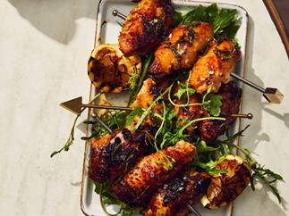 Skewers of barbecued chicken wings and lemon halves on a white rectangle tray, on an off-white marble table