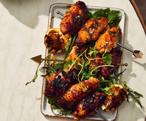 A rectangle plate holding skewers of charred, sticky chicken wings garnished with green herbs and a charred lemon half.