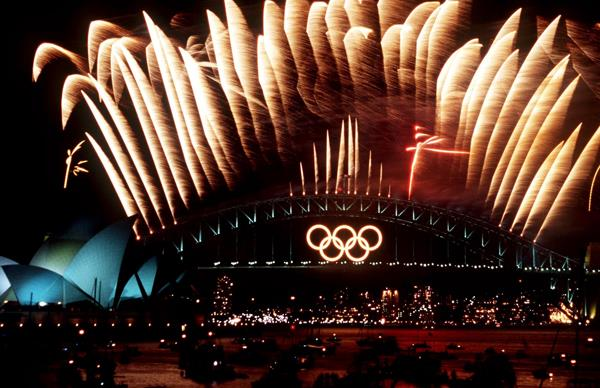 The Sydney Harbour Bridge at nighttime, with a neon-light of the Olympic Games logo, and yellow fireworks firing from the top of the bridge.