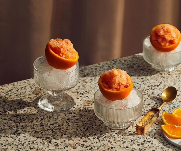 Three crystal glass cups filled with shaved ice, topped with hollowed-out orange halves filled with orange granita.