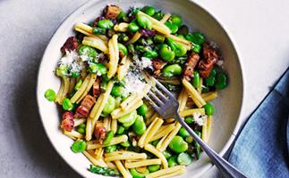Bird's eye view shot of a white bowl holding pasta, broad beans and chopped pancetta, with a silver fork inside.