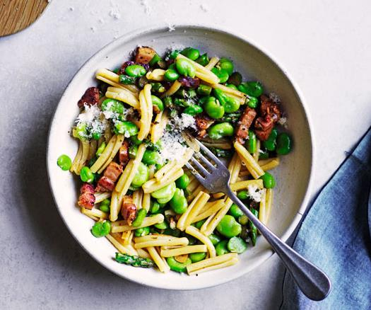 White bowl holding a mixture of short pasta, broad beans, asparagus and pancetta, with a steel fork inside, and a blue napkin to the side.