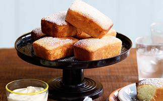 Rectangular lemon cakes piled onto a black cake stand.