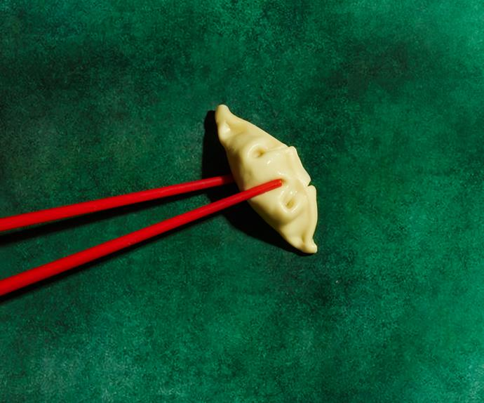 A single dumpling, grasped in a pair of red chopstick, on a dark green background.