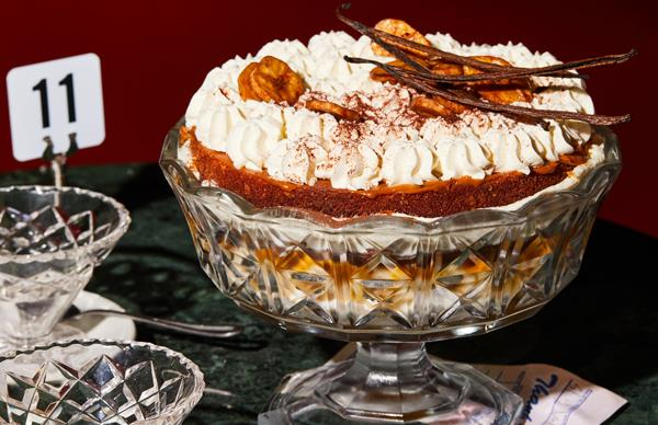 Ornamental glass bowl on a stand holding a trifle topped with whipped cream, banana chips and vanilla bean pods