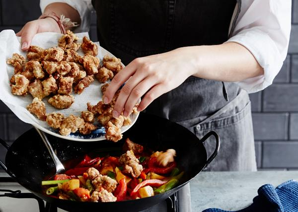 A chef adding fried pieces of pork into a wok on a stove, that's already filled with sliced capsicums and spring onions.