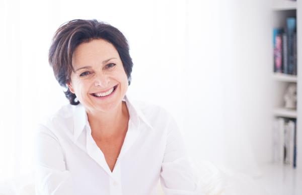 Publisher Julie Gibbs smiling in a white button shirt, with a white background and a bookshelf in the background.