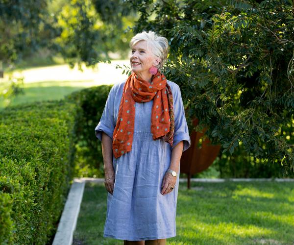Maggie Beer in a blue smock dress and orange scarf, standing in a garden, looking up and away from the camera