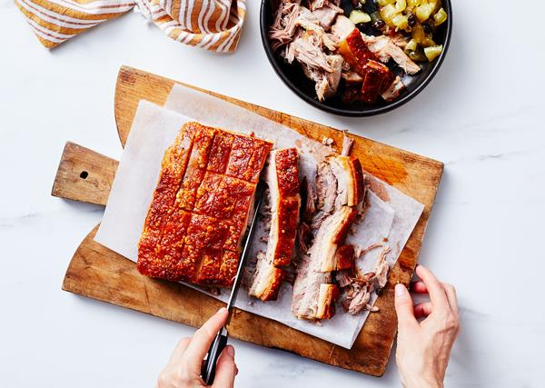 A slab of pork belly with golden-brown crackling being sliced into long, elegant pieces