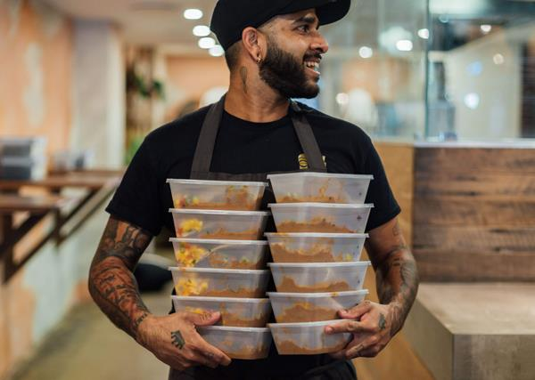 A man in a black T-shirt and black cap, holding two stacks of plastic containers filled with cooked meals.